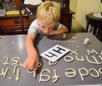 small boy with clay letters