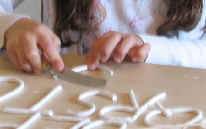 child molding letters with clay