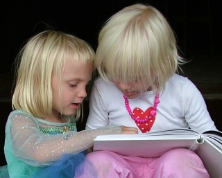 two small girls with book